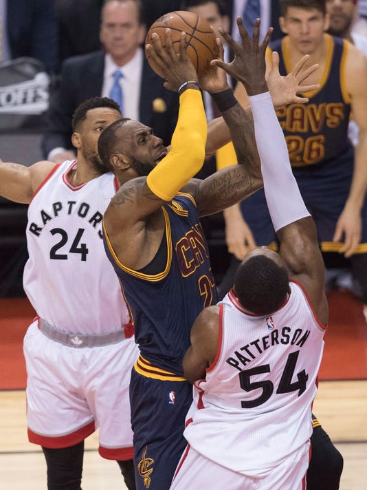 Cleveland Cavaliers' LeBron James, center, drives to the basket between Toronto Raptors' Norman Powell, left, and  Patrick Patterson during the first half of Game 3 of an NBA basketball second-round playoff series in Toronto on Friday, May 5, 2017. (Fred Thornhill/The Canadian Press via AP)
