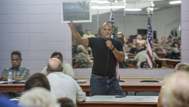 Chalan Pago resident Adrian Gogue holds up a photo as he speaks out against a zone variance requested by the developers of the Pago Bay Marina Resort project during a meeting at the Yona Community Center on Wednesday, Jan. 6. Developers, Guam Wangfang Construction Company working with consultant FCB Planners, were met with strong opposition to construction of the 304-unit structure, consisting of a 14-story and a 15-story residential tower, to be built near the mouth of the Pago River.