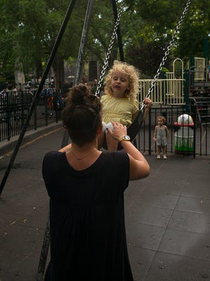 A woman pushes a young girl on a swing set in an unidentified public park, Brooklyn, New York, New York, June 27, 2016. (Photo by Robert Nickelsberg/Getty Images)