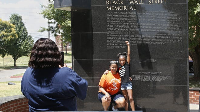 Katrina Cotton, center, of Houston, poses for a photo with her daughter, Kennedy Cotton, age seven, as her aunt, Janet Wilson, left, takes the photo Monday at the Black Wall Street memorial in Tulsa, Okla.