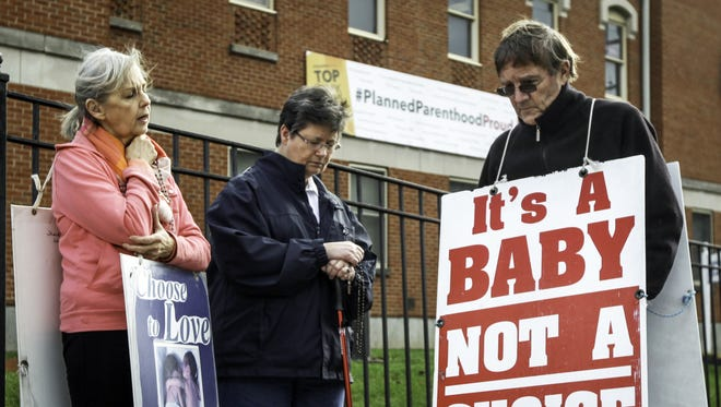 (From left): Julia Gieske, Kathy Thamann and Blaine Comfort of Fort Mitchell join in a prayer circle Monday outside the Planned Parenthood building on Auburn Street.