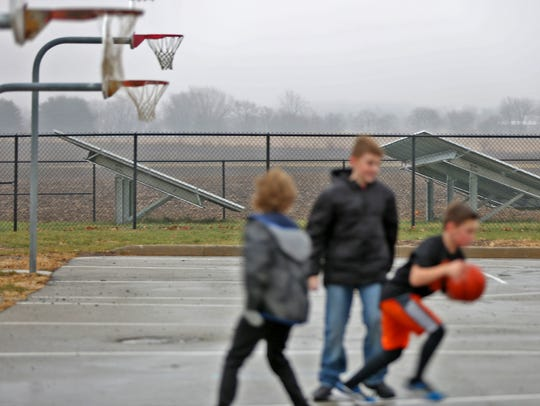 Kids play on the playground as solar panels work nearby,