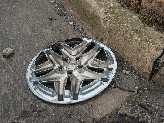 Several wheel covers lay near the curb, jolted from