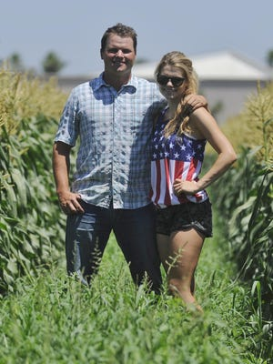 Jacob and Jaclyn te Velde, brother and sister, stand in the middle of their corn field, where they pick corn each morning and sell to people across the Valley.
