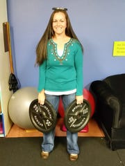 Kristen Meeker holding 93 pounds of free weights, the amount she lost on her journey between January and November of 2015.