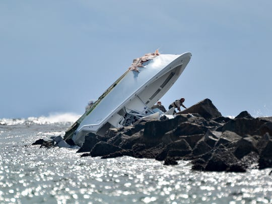 Investigators inspect an overturned boat as it rests on a jetty after a crash Sunday off Miami Beach, Fla. Authorities said that Miami Marlins starting pitcher Jose Fernandez was one of three people killed in the crash.