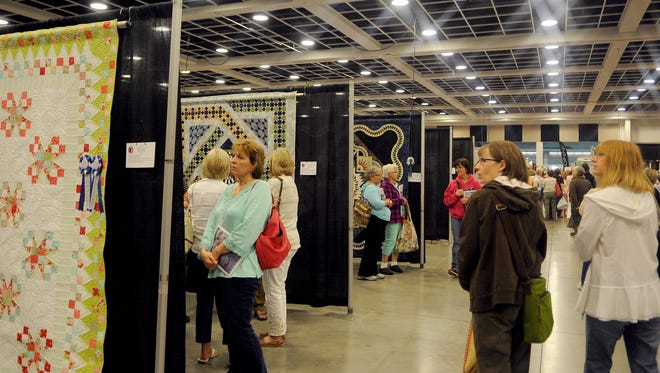 Attendees look at some of the 'Best of Show' quilts during the quilting conference and show Thursday at the River's Edge Convention Center in St. Cloud.