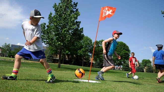 Eli Perry, 9, uses his heel to kick the ball into the 18th hole during a free demonstration at Angushire Golf Club in Waite Park.
