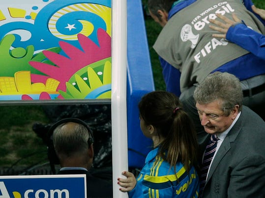 England's manager Roy Hodgson, bottom right corner, leaves the pitch after losing 1-2 to Uruguay during the group D World Cup soccer match between Uruguay and England at the Itaquerao Stadium in Sao Paulo, Brazil, Thursday, June 19, 2014.  (AP Photo/Michael Sohn)