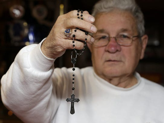 In this 2014 photo, Ronald Ziolecki holds a rosary
