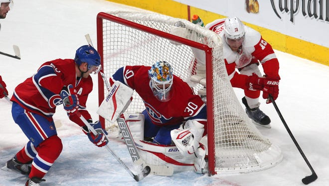 Detroit Red Wings center Joakim Andersson (18) shoots on goal against Montreal Canadiens goalie Peter Budaj (30) as defenseman Andrei Markov (79) defends during the first period at Bell Centre.