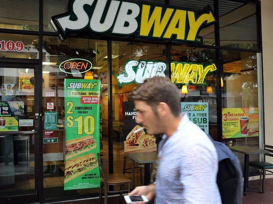 A pedestrian walks past a Subway restaurant in Miami in October. Subway named former Coca Cola executive Joe Tripodi as its new chief marketing officer Thursday, after Tony Pace left the position to start his own company.