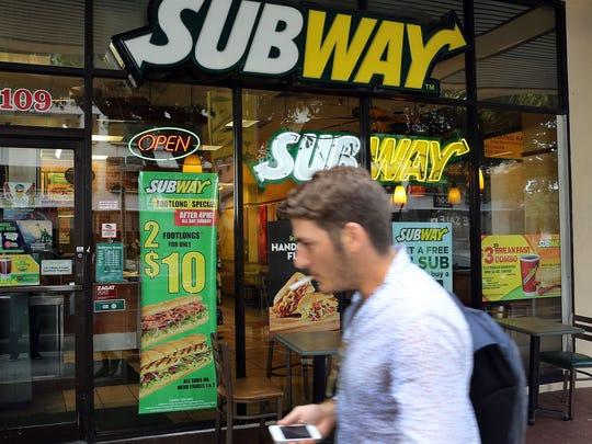 A pedestrian walks past a Subway restaurant in Miami