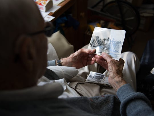 """Herbert """"Mac"""" MacMillan looks through old photographs from while he served in WWII in his room at Brookdale Greenville Senior Living Community on Wednesday, Oct. 25, 2017."""