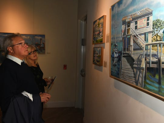 "Steve and Sally Bataran look over paintings of the old days on Marco. The Marco Island Historical Museum opened an exhibit Wednesday evening called ""Coastal Trade,"" featuring paintings and artifacts from the collection of artist Paul Arsenault."