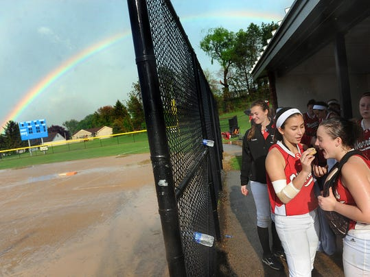 It's rain delays and rainbows as Susquehannock's Maddy Staub shares a cookie with teammate Lily Yoakum while the duo wait for the field to be cleaned up during their game against Kennard-Dale in Spring Grove on Monday, May 12, 2014. (File -- GameTimePA.com)