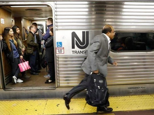 An afternoon rush-hour commuter rushes to board a crowded NJ Transit train at Penn Station.