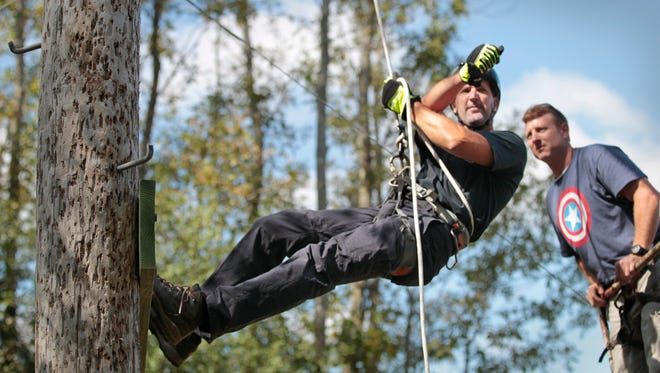 Monroe County Probation officer Bob Masucci stops mid-rappel and practices taking aim at a target while hanging as officers do a walk-through of the course for the Best Cop Competition on Friday.  The contest features two-person teams competing over a timed obstacle course.  The day-long event is being held at the Competition Grounds on Fox Road in Farmington.