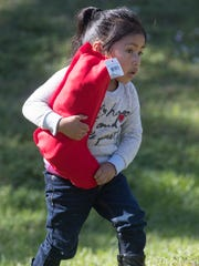 Juana Esteban, 5, holds on tightly to a gift given at the Nations Association Charities Holiday meal at Schandler Park in Fort Myers on Monday.
