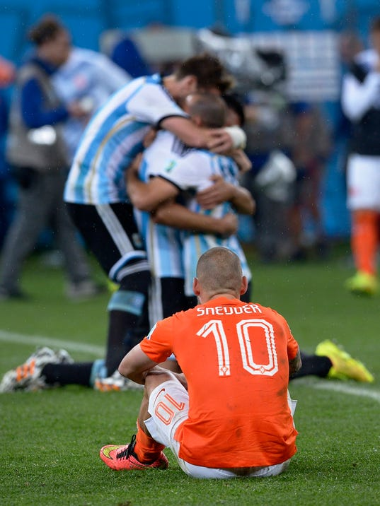 Netherlands' Wesley Sneijder watches as Argentina players celebrate after winning a shootout at the end of the World Cup semifinal soccer match between the Netherlands and Argentina at the Itaquerao Stadium in Sao Paulo Brazil, Wednesday, July 9, 2014. Argentina won 4-2 on penalties after the match ended 0-0 after extra time.  (AP Photo/Manu Fernandez)