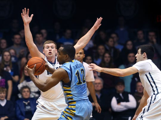 Austin Etherington tries to block Marquette's Derrick Wilson in the closing seconds of the first half at Hinkle Fieldhouse in Indianapolis on Wednesday, Feb. 25, 2015.