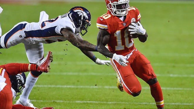 Kansas City Chiefs wide receiver Tyreek Hill gains yardage in the second quarter, slipping past the defense of Denver Broncos strong safety Kareem Jackson on Sunday, Dec. 6, 2020, at Arrowhead Stadium in Kansas City, Mo.