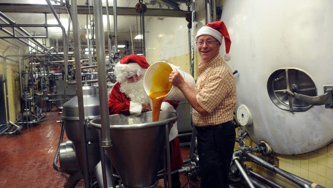 Lewes Dairy President Chip Brittingham, with some help from Santa, working on the Christmas in July eggnog batch.