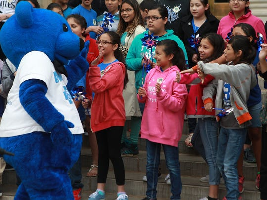 The blue bear mascot for the Children's Advocacy Center of Tom Green County high fives students from Reagan and Glenn Middle School who showed up to support victims of child abuse on the steps of the county courthouse Tuesday morning. The center held its annual Pinwheel Ceremony, which represented 447 confirmed cases of child abuse and neglect in the county.Michelle Gaitan/Standard-Timesshot/archived 0412