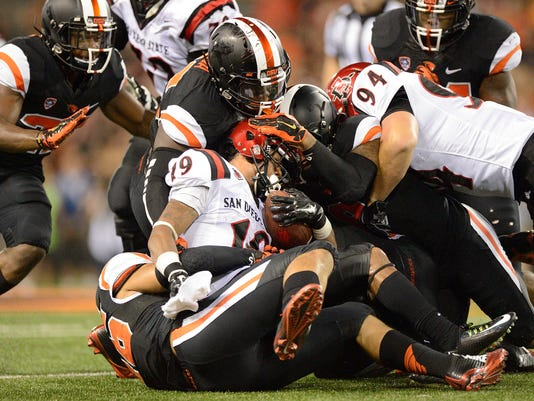San Diego State tailback Donnel Pumphrey (19) runs into a wall of Oregon State defenders during the first quarter of an NCAA college football game in Corvallis, Ore., Saturday, Sept. 20, 2014. (AP Photo/Troy Wayrynen)
