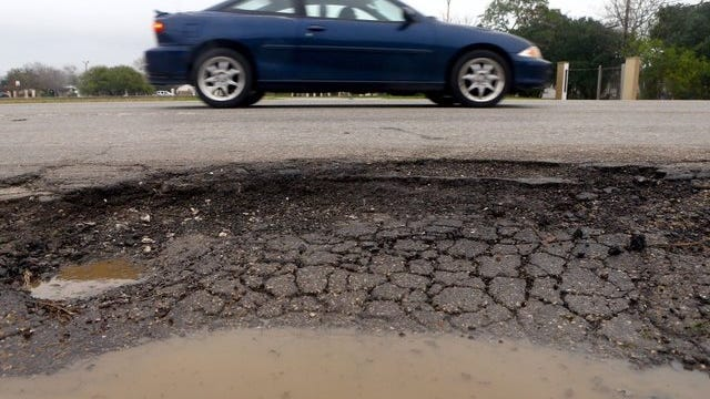 GABE HERNANDEZ/CALLER-TIMESA vehicle drives past a pothole located near a bus stop on South Staples Street on Thursday.