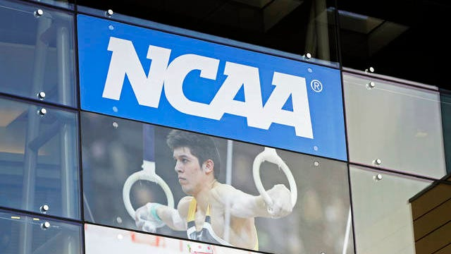 In this photo, the NCAA headquarters is shown in Indianapolis. College athletes will no longer need permission from their coach or school to transfer and receive financial aid from another school. The NCAA Division I Council approved the change on Wednesday, and it takes effect on Oct. 15.