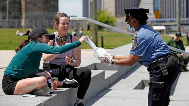 A New York Police Department school safety officer hands out face masks to women at Brooklyn Bridge Park during the coronavirus pandemic, Sunday, in New York.