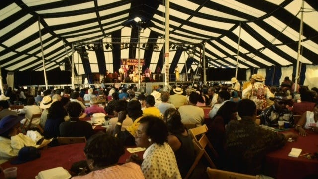 An audience listens to music inside the striped Downtown Festival Tent in this photo from the mid-1990s.