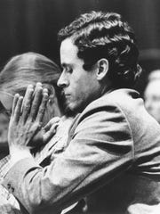 Ted Bundy presses his palms together as judge Edward