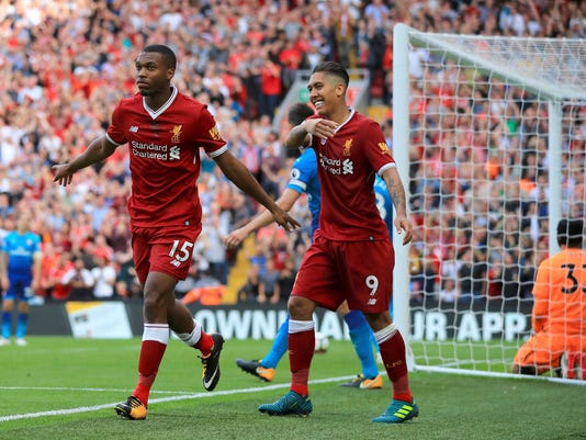 Liverpool's Daniel Sturridge, left, celebrates scoring his side's fourth goal of the game against Arsenal during their English Premier League soccer match at Anfield, Liverpool, England, Sunday Aug. 27, 2017. (Peter Byrne/PA via AP)