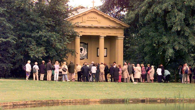 Visitors crowd around the lakeside Doric Temple memorial to Princess Diana at Althorp on July 1, 1998, in Northamptonshire.
