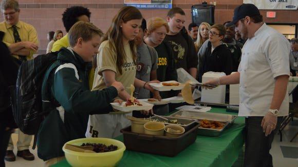 Ronnie Burkle, SoDel Concepts chef, serves Indian River High School students gourmet fish stick tacos.