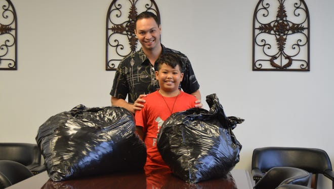 Isaiah Baza, front, was one of the first Guam residents to drop off a donation for Typhoon Soudelor relief at Sen. Michael San Nicolas' office in Hagatna Tuesday.