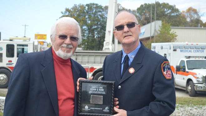 Gary Deaton is presented with a commemorative piece of steel from the World Trade Center by retired New York City firefighter John Turkus for Deaton's contribution to the Building for America's Bravest project.