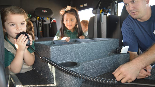 While taking a tour of the new Newfield Fire Truck during Fire Safety Week at Edgarton Christian Academy, Alivia Oliver, 4, of Vineland, wasted no time trying out the radio. Fire Chief Sean Riley recognized an aspiring firefighter as Mya Pesantes, 4, of Newfield looked on.