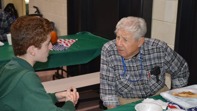Eighth grader Joseph Lopresti, 13, of Vineland listens intently as Veteran Milton J. Dragon shares his stories of the U.S. Navy Fleet Air Wings during a soup luncheon for veterans at Edgarton Christian Academy.