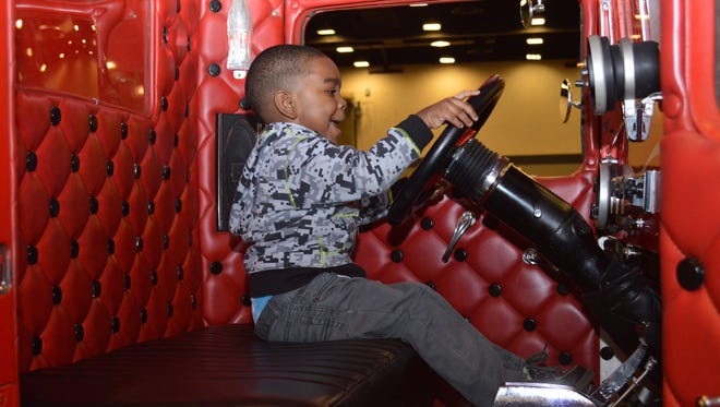 Roman Lewis climbs into Larry Nichols' Red 1934 Ford Truck at the Racing Vehicle Extravaganza on Sunday at the Mississippi Trade Mart.  More than 180 vehicles from states across the mid-south were on display.