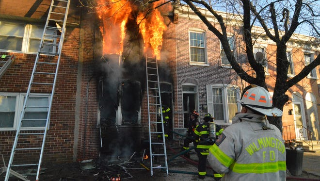 A fire burns a row house on North Monroe Street in Wilmington on Tuesday.