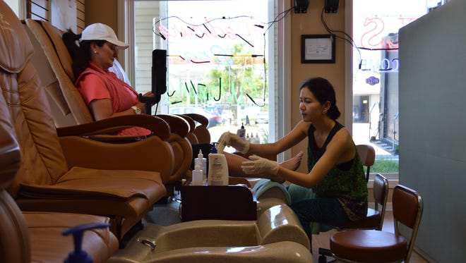 Heather Nguyen, co-owner of Breeze Nails Bar, gives a new client a pedicure.