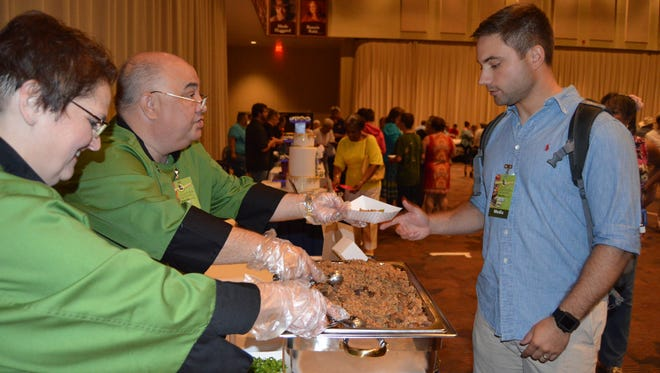 """A guest of Paragon's La Cuisine event samples chicken and sausage jambalaya, from Mr. Roger's Blue Plate. At the 13th annual """"Cuisine de la Louisiane"""" fundraiser, guests were offered a taste of delicious meals from over 20 restaurants from Central Louisiana."""