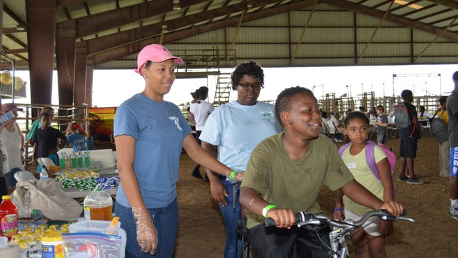 Tensas Elementary fourth-grader Thomas Mason uses peddle power to make a healthy smoothie. Regional 4-H Teen Leaders Precious Richardson, left, and Sydney Cephus, center, demonstrated the popular bike blender at the Wild About Tensas celebration held on Aug. 11 in celebration of National Health Center Week.