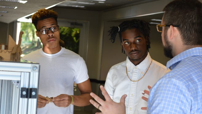 Jaylan Tate, left, and Keon Mack, center, seniors at Austin-East Magnate High School, talk to Zach Machanoff of the Visionary Center for Sustainable Communities about technologies in manufacturing Thursday, Oct. 6, 2016, at Community Manufacturing Days.