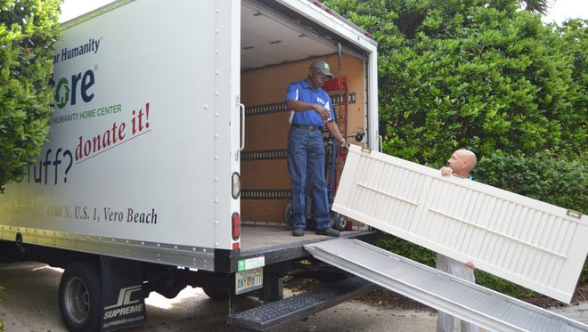 The Hill Group's Steve Burris and Habitat driver Glenn Miller load a salvaged louvered door onto the Habitat ReStore truck