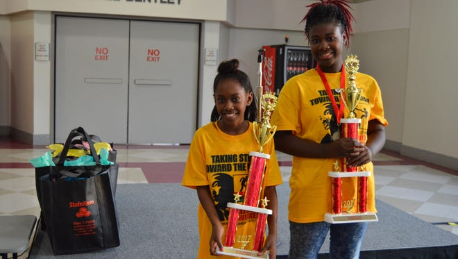 Faith Williams (left) and Salaycia Williams (right) pose with their trophies after being named the spelling bee champions for fourth- and fifth-grade.