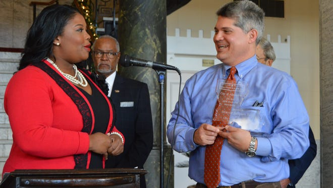 """Tonia Moore, director for the Louisiana campaign for Tobacco Free Living presents Mayor Jacques Roy with a plaque, thanking the city of Alexandria for five successful years of being a """"smoke-free"""" city."""